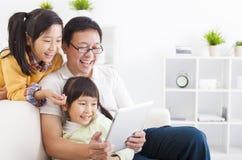 pai que usa o PC da tabuleta com meninas Fotos de Stock Royalty Free