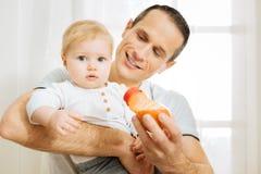 Pai responsável atento que oferece a sua criança uma garrafa e que sorri alegremente Fotografia de Stock Royalty Free