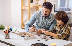 Pai sério e filho que fazem a imagem dos enigmas Foto de Stock Royalty Free