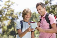 Pai And Son Hiking através do campo imagens de stock