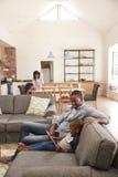 Pai And Son Sit On Sofa In Lounge que usa a tabuleta de Digitas foto de stock royalty free