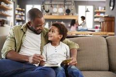 Pai And Son Sitting em Sofa In Lounge Reading Book junto imagens de stock