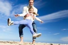 Pai Swinging Daughter na praia Fotografia de Stock