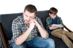 Pai virado e filho que sentam-se no sofá após a discussão foto de stock