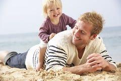 Pai And Young Daughter que senta-se na praia junto Fotos de Stock Royalty Free