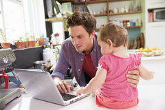 Pai With Young Daughter que usa o portátil na cozinha Fotografia de Stock