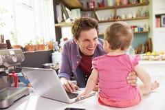 Pai With Young Daughter que usa o portátil na cozinha Imagem de Stock Royalty Free