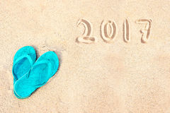 Paia dei Flip-flop sulla spiaggia, 2017 scritto nella sabbia Fotografie Stock