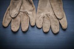 Paia dei guanti di lavoro protettivi sul bordo di legno Fotografia Stock