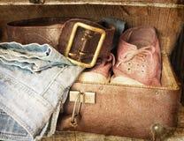 Paia dei jeans, scarpe, cinghia in una valigia d'annata Immagine Stock Libera da Diritti