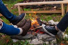 3 paia dei piedi che si scaldano le loro scarpe intorno ad un'aria aperta del fuoco del campo in autunno immagine stock