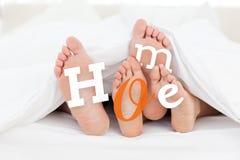 Paia dei piedi sotto il piumino con testo domestico Fotografia Stock