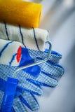 Paia dei rulli di pittura dei guanti di sicurezza su fondo bianco fotografie stock libere da diritti