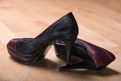Tacchi alti rossi neri sul pavimento di legno Immagine Stock