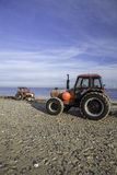 Paia dei trattori rossi sulla spiaggia Immagine Stock