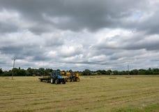 Paia dei veicoli di agricoltura veduti raccogliere le balle di paglia su un campo arabile Fotografie Stock