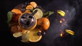 Paia dei vetri con il vino della bevanda della bevanda alcolica e del narghilé con i frutti stock footage