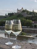Paia dei vetri di vino bianco sulla parete di pietra con paesaggio nella b Fotografie Stock Libere da Diritti
