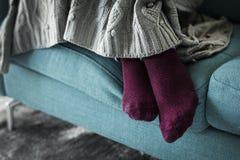 Paia del primo piano delle gambe sul sofà fotografia stock libera da diritti