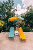 Paia delle chaise-lounge del sole e di un ombrello di spiaggia su una piscina con le montagne e le nuvole nei precedenti perfetto fotografia stock