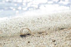 Paia delle fedi nuziali dell'oro sulla spiaggia di sabbia dal mare fotografie stock libere da diritti