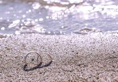 Paia delle fedi nuziali dell'oro sulla spiaggia di sabbia dal mare fotografie stock