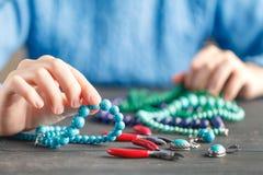 Paia delle mani e delle pinze che montano una collana della perla Fotografia Stock