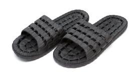Paia delle pantofole di plastica nere su bianco fotografie stock
