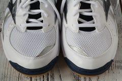 paia delle scarpe bianche di sport su fondo di legno, paia di Sn bianco Fotografia Stock