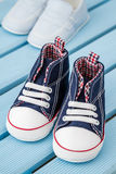 Paia delle scarpe da tennis blu scuro e bianche del bambino e delle scarpe di bambino blu Immagini Stock Libere da Diritti