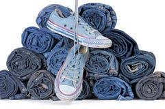 Paia delle scarpe da tennis e della pila blu di jeans colorati rotolati Fotografie Stock Libere da Diritti