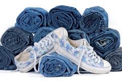 Paia delle scarpe da tennis e della pila di jeans colorati rotolati Immagini Stock Libere da Diritti