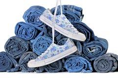 Paia delle scarpe da tennis e della pila di jeans colorati rotolati Fotografia Stock Libera da Diritti