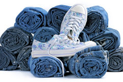 Paia delle scarpe da tennis e della pila di jeans colorati rotolati Fotografia Stock