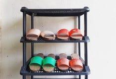 Paia delle scarpe di legno tradizionali casalinghe sul portascarpe Immagine Stock