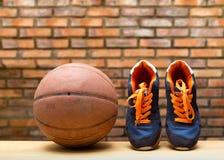Paia delle scarpe di sport e della palla di pallacanestro Fotografia Stock