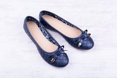 Paia delle scarpe piane del ` blu scuro delle signore su fondo di legno bianco Immagine Stock