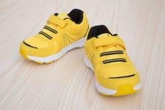 Paia delle scarpe sportive gialle per il bambino Immagini Stock