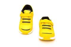 Paia delle scarpe sportive gialle per il bambino su bianco Fotografia Stock