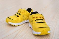 Paia delle scarpe sportive gialle per il bambino su legno Fotografia Stock Libera da Diritti