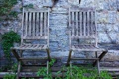 Paia delle sedie di giardino di legno invecchiate contro una parete di pietra con la crescita delle piante Fotografie Stock