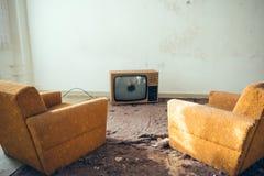 Paia delle sedie in disuso del sofà davanti alla TV rotta Fotografie Stock