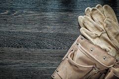 Paia di cuoio della cinghia della costruzione dei guanti protettivi sul bordo nero Immagine Stock