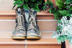 Paia di vecchi stivali indossati al gradino della porta Immagine Stock Libera da Diritti