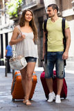 Paia felici con bagagli che camminano nella città Immagine Stock