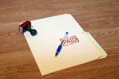 Paid. Office series with stamp and pad on desk with folder and pen. Room for text or logo stock photos