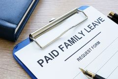 Paid family leave form in clipboard and notepad. Paid family leave form in clipboard and note pad stock image