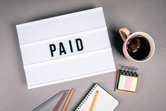 Paid. Text in light box stock photography