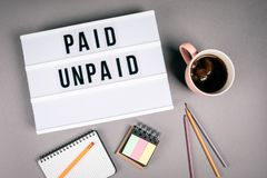 Paid and Unpaid. Text in light box stock photography