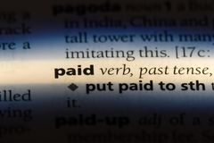 Paid. Word in a dictionary.  concept royalty free stock photo